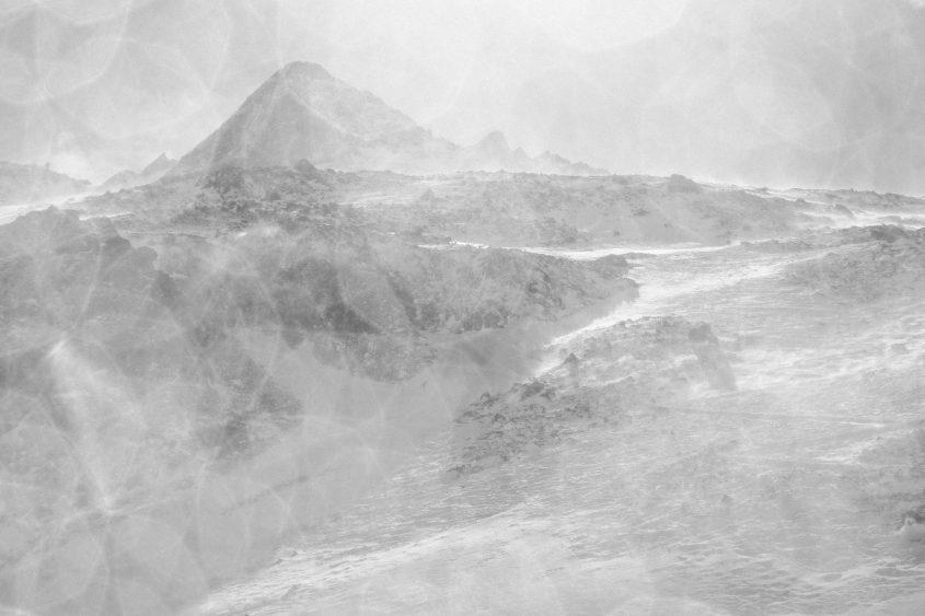 Starke Windböhen wirbeln viel Schnee auf welcher den Gipfel verschleihert. Im Gegenlicht bilden sich fazinierenden Schneekristalle um den Gipfel. Kühtai, 2017.